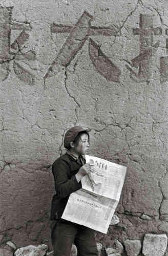 """Province du Henan, Chine, 1965 : « Cette jeune paysanne sort de la cantine et lit """"LaJeune Chine"""".»"""
