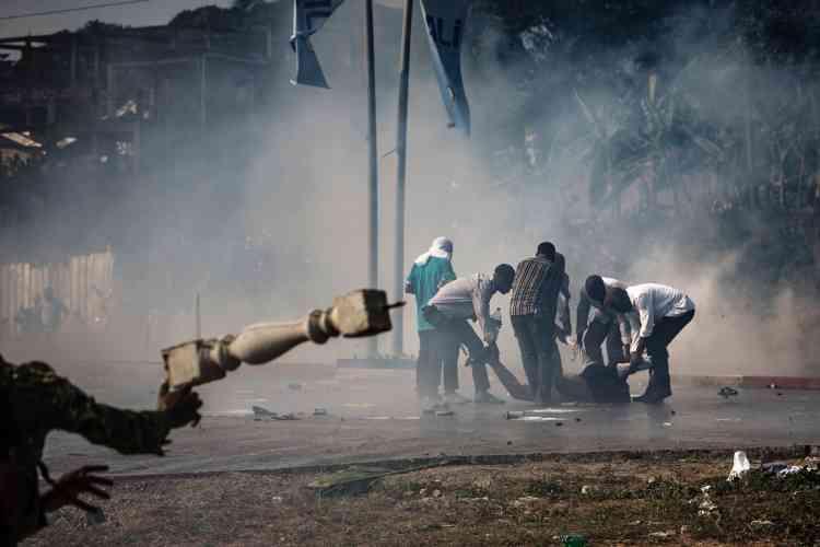 Des partisans de l'opposition portent secours à l'un des leurs, blessé lors d'affrontements avec la police, le 31 août 2016.