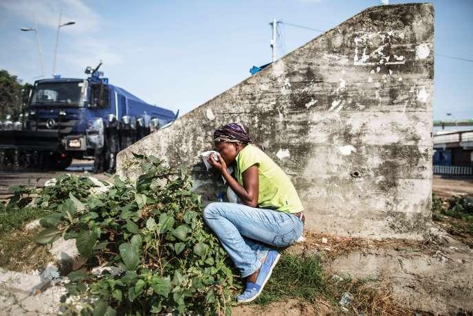Une femmese protège des gaz lacrymogènes tirés par les forces de l'ordre contre des opposants à Ali Bongo, à Libreville, le 31 août.
