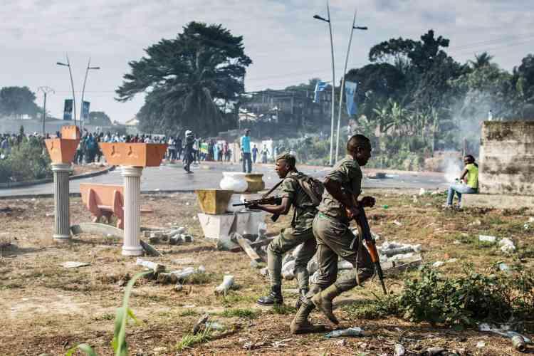 Des soldats gabonais courent lors d'affrontements avec des partisans de l'opposition le 31 août 2016.