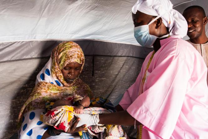 Sous la tente mobile de l'Unicef, une sage-femme ausculte le bébé d'une jeune femme déplacée qui a fui les tueries de Boko Haram.