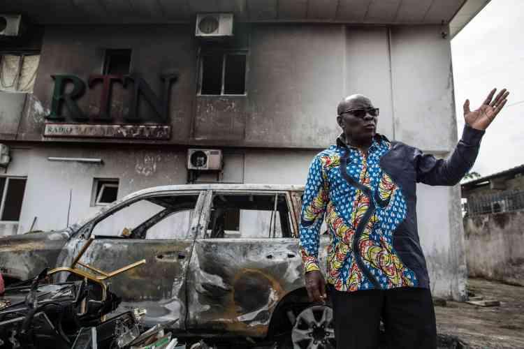 Le patron de la télévision RTN devant sa voiture et les studios de sa chaîne, attaqués après l'annonce des résultats officiels, le 31 août 2016.