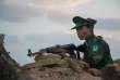 Un soldat de la TNLA monte la garde devant une pagode dont la construction a été financé par le groupe.