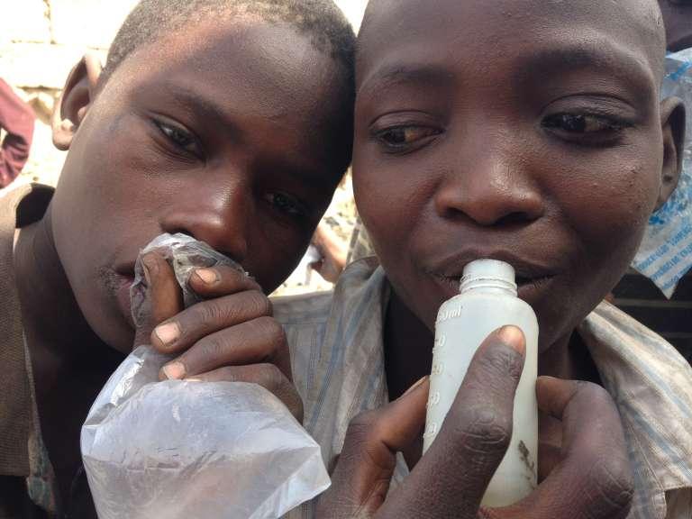 Deux enfants de Kano sniffent de la colle.