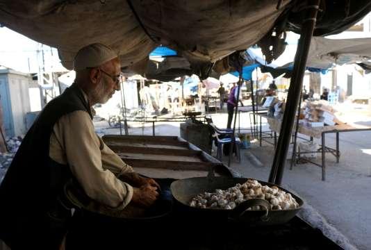 Un vieil homme vend de l'ail dans un marché désert d'une zone tenue par les rebelles près d'Alep, le 8 septembre.