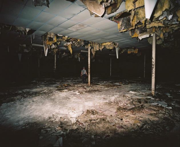 Dans une salle délabrée de l'usine désaffectée, de la laine de roche pend du plafond.