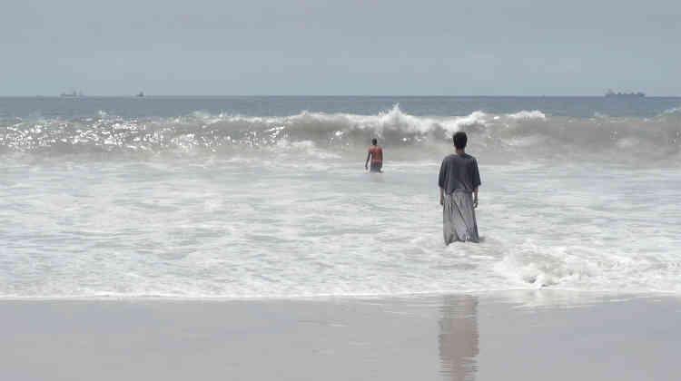 «Une vidéo d'Emmanuel Trousse explore le thème difficile de l'impossible voyage de certains migrants africains pour rejoindre les côtes européennes.A peine apparus dansles vagues, les corps s'évanouissent à l'horizon.»
