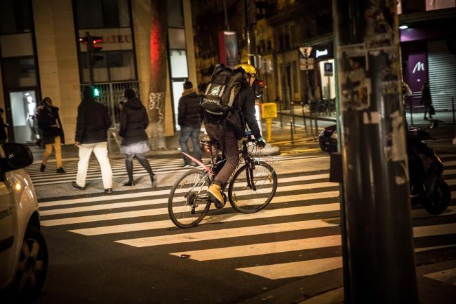 Un coursier à vélo livre des repas pour la société Deliveroo, le 14 février à Paris.