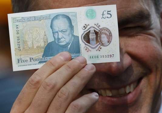 Le gouverneur de la Banque d'Angleterre, Mark Carney, pose avec un nouveau billet de cinq livres sterling en polymère, le 13 septembre.