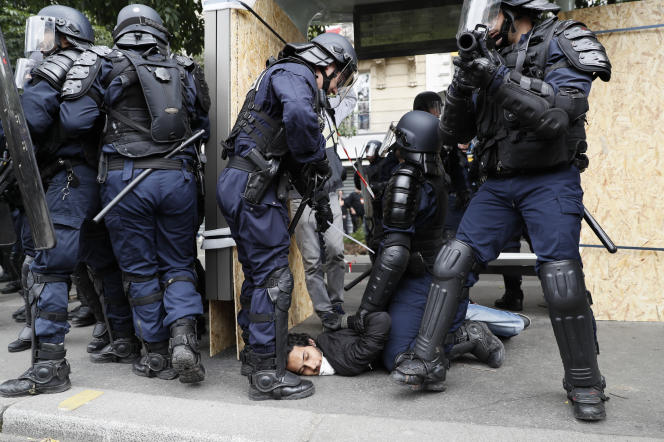 Des policiers tiennent un manifestant à terre, le 28 juin.