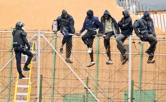 Des migrants africains font face à un garde civil espagnol, en haut de la barrière séparant le Maroc et l'enclave de Melilla.