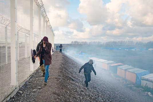 Des migrants fuient les gaz lacrymogènes, le long du port de Calais.