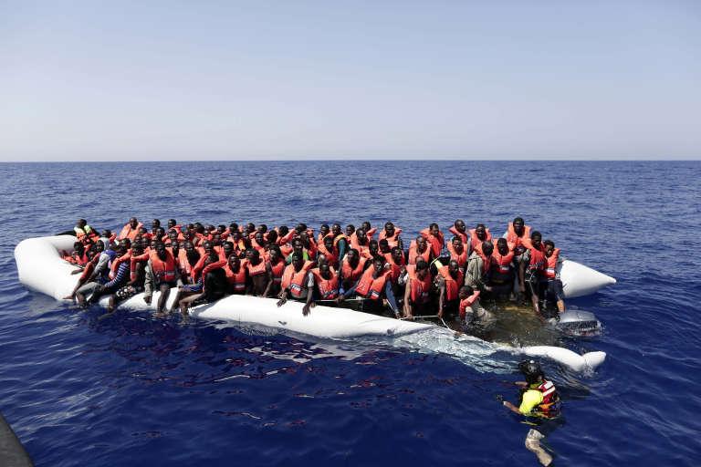 Des migrants en provenance d'Afrique subsaharienne, le 18 août 2016, sont secourus par la Croix-Rouge au large de la Libye.