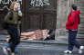 Des piétons passent devant une personne dormant dehors, le 2 septembre à Buenos Aires en Argentine.