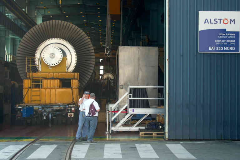 (FILES) This file photo taken on June 23, 2014 shows employees of the French power and transport engineering company Alstom standing by a steam turbine parked in a workshop in Belfort. France's Socialist government clashed with trainmaker Alstom on September 13, 2016 over the company's plans to close a historic plant, throwing into focus the state's policy of intervening to shore up a shrinking manufacturing base. Alstom, which is 20-percent owned by the state, announced last week it would halt production at the factory in Belfort in eastern France by 2018. French Prime Minsiter Manuel Valls said the government was determined to keep the plant open and was working to generate new orders for a site where 400 people are employed. / AFP / SEBASTIEN BOZON