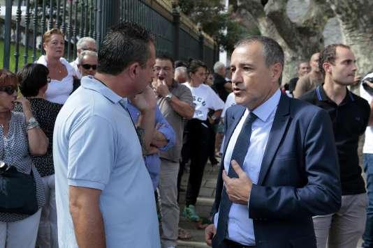 Le président de l'Assemblée de Corse, Jean-Guy Talamoni discute avec des manifestants rassemblés à l'extérieur du palais de justice de Bastia, le 15 septembre.