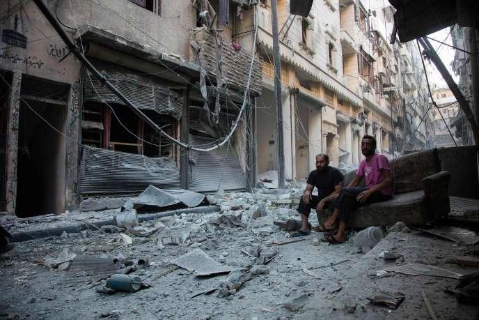Des habitants d'Alep contemplent les débris après des frappes, dimanche 18 septembre.