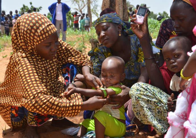 Des mères utilisent un bracelet MUAC pour lutter contre la malnutrition, dans le village de Barago, au Niger, le 14 juillet 2016.