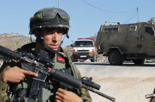 Les forces israéliennes assurent la sécurité du site où un Palestien a été abattu, aucheckpoint situé à l'entrée de Bani Naïm, ville voisine d'Hébron.