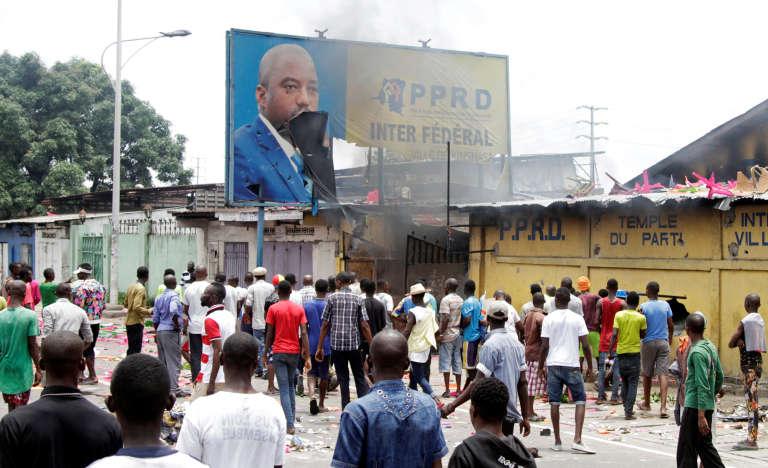 Des manifestants détruisent une affiche de Joseph Kabila, lundi 19 septembre, à Kinshasa.