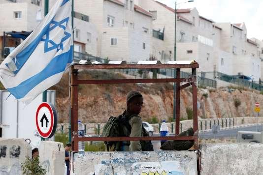 Un soldat israélien à l'entrée de la coloniede Kiryat Arba. Elle jouxte Hébron, une poudrière où 500 colons israéliens vivent retranchés sous haute protection de l'armée, au milieu de 200 000 Palestiniens.