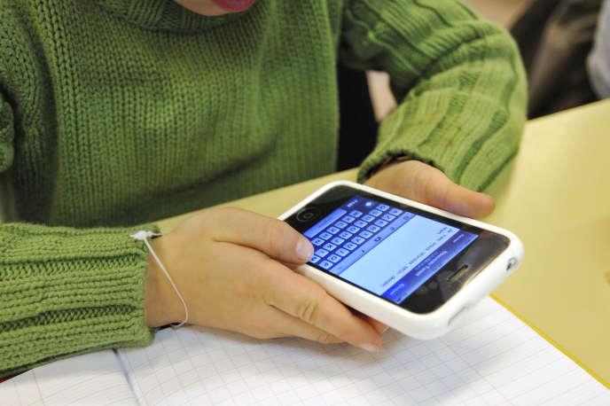 Un élève de CE1 écrit un message sur un téléphone portable lors d'une leçon sur le fonctionnement de Twitter, le 5 décembre 2011 à l'école privée Immaculée Conception de Seclin.