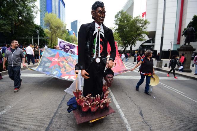 Une figurine représentant le président Peña Nieto planté sur les mains des 43 disparus d'Iguala, lors d'une manifestation à Mexico, le 26 septembre 2016.