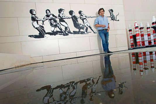 Xavier Prou, connu sous le pseudonyme Blek le Rat, pose devant le Tug of Wall, à Dubai.