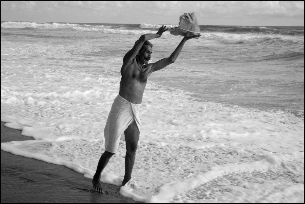 « Dans la station balnéraire de Varkala, en Inde, cet homme confie aux vagues les cendres ainsi que trois os d'un proche parent, seize jours après sa crémation. La tradition veut que les cendres soient confiées à de l'eau courante, souvent celle d'une rivière».