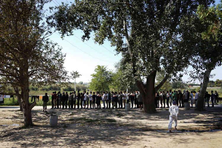 Les hommes font la queue en attendant le service du déjeuner.