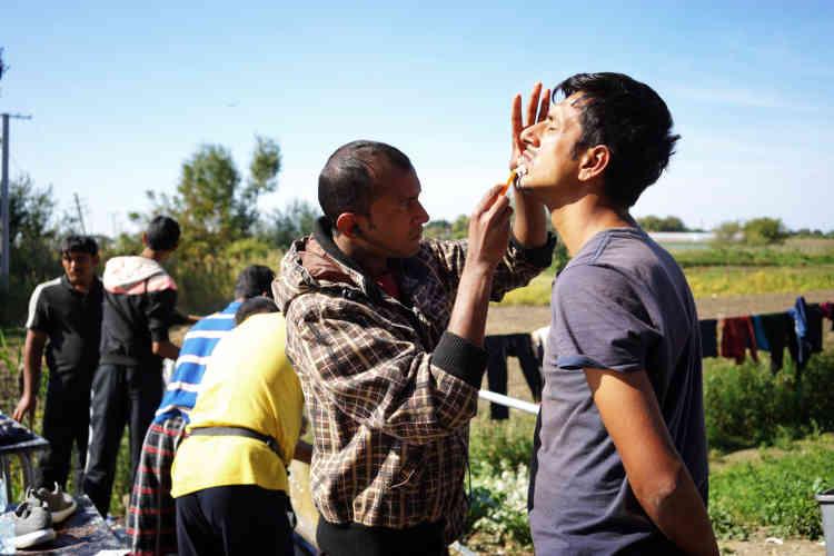 Des migrants se rasent à tour de rôle.