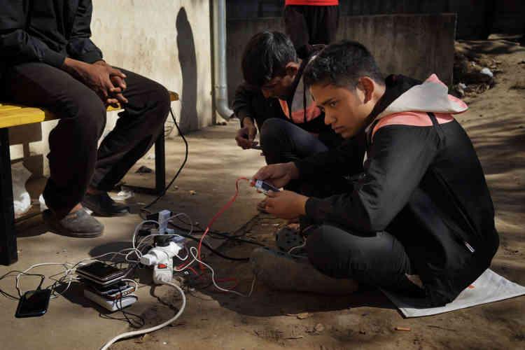 Des migrants chargent la batterie de leur téléphone.
