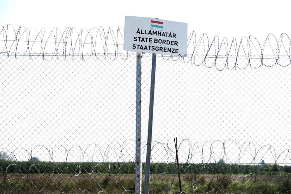 Un panneau sur la clôture annonce la frontière qui sépare la Hongrie de la Serbie.
