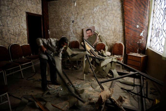 Un homme nettoie une chambre après une explosion, le 11 juin, à Damas.