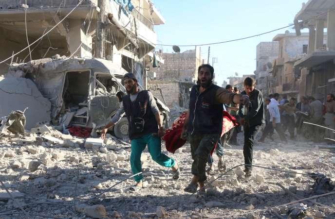 Des volontaires syriens transportent un blessé sur une civière après un frappe aériennedes forces gouvernementales, dans le quartier de Heluk à Alep, le 30 Septembre.