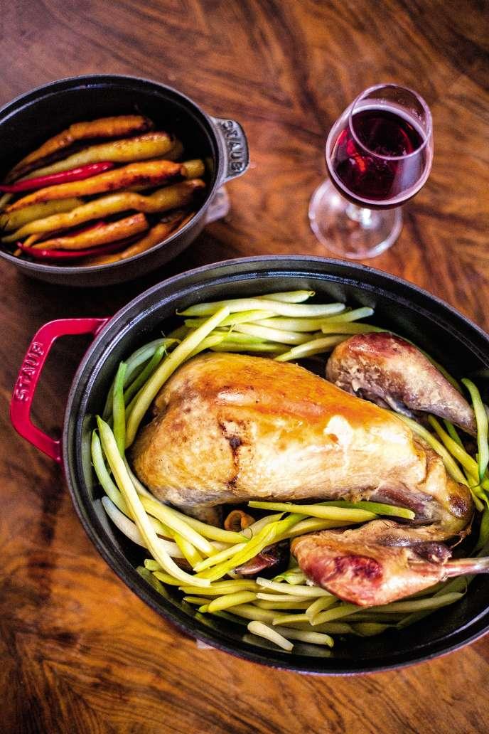 Pintade au four, accompagnée de haricots jaunes, de carottes et d'un verre de vin.