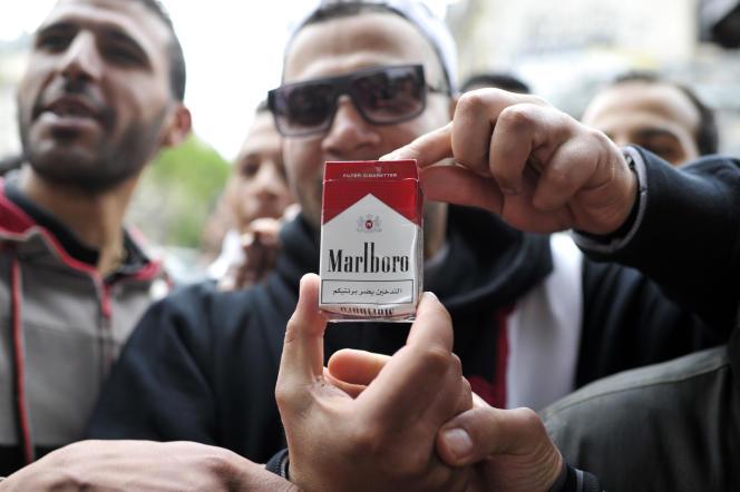 Des vendeurs de cigarettes algériennes montre un paquet de contrebande dans le quartier de Barbès à Paris, le 22 mai 2013.