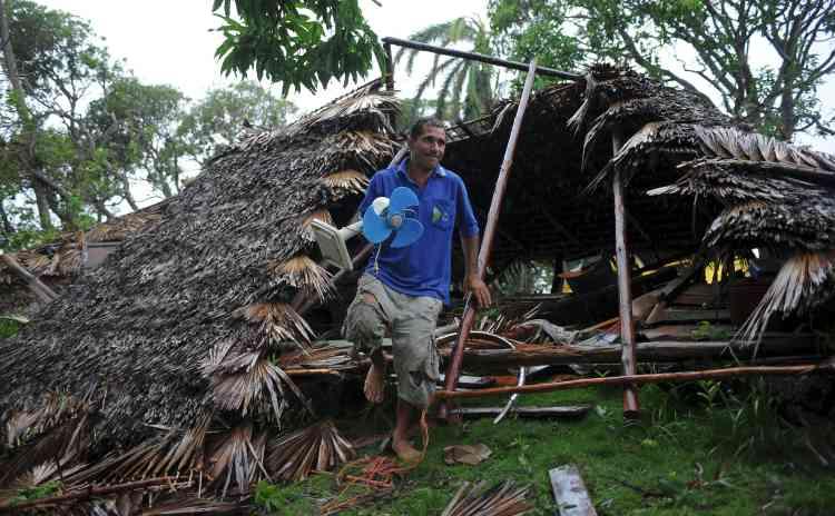 Un habitant de la région de Guantanamo, à Cuba, rassemble ses effets personnels hors de sa maison détruite.