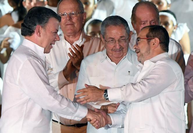 Le président colombien Juan Manuel Santos (à gauche) et le leader des FARC, Rodrigo Londono (à droite) se félicient avec le président cubain, Raul Castro (au centre), après la signature d'une accord de paix signé àCartagena, Colombie, le26septembre2016. Juan Manuel Santos a reçu le prix Nobel de la paix le7octobre2016 pour ses efforts en faveur de la paix.