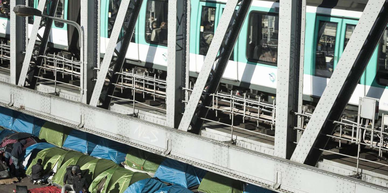 Des lignes de tentes où des migrants africains vivent dans le centre de Paris, sous la ligne de métro à proximité de la Gare du Nord, la plus grande gare d'Europe. Beaucoup des migrants sont en transit, et attendent de se rendre à Sangatte, avant de traverser la Manche pour rejoindre l'Angleterre.  Photo (c) Ed Alcock / M.Y.O.P. 3/2/2015  Lines of tents where mostly african migrants are living in central Paris, beneath the metro line that runs above ground near to the Gare du Nord, Europe's largest train station. Many of the migrants are in transit, waiting to travel north to Sangatte, and accross the channel to England.  Photo (c) Ed Alcock / M.Y.O.P. 3/2/2015