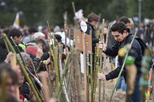 Protesters plant wooden staffs during a demonstration against a controversial airport project near Nantes on October 8, 2016 in Notre-Dame-des-Landes, western France.  Protesters have been engaged in a 15-year legal battle to block the construction of a major new airport on swampland outside the western city of Nantes. Approved in 2008, the 580-million-euro (747 million USD) project had been due to start in 2014 but has been repeatedly delayed due to fierce opposition by environmental protesters. / AFP / JEAN-SEBASTIEN EVRARD