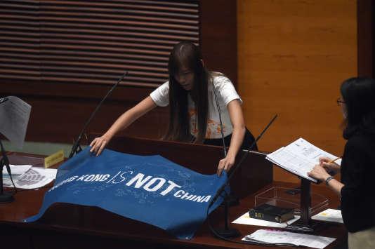 La députée Yau Wai-ching, 25 ans, étend une banderole sur laquelle est écrit «Hongkong n'est pas la Chine», le12octobre2016.