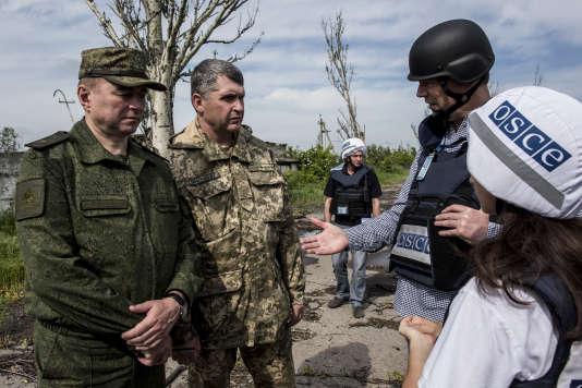 Alexander Hug, chef adjoint principal de la mission d'observation de l'OSCE, avec des représentants du Joint Center for Control and Coordination, structure installée sur le territoire ukrainien et regroupant des officiers ukrainiens et russes, le 27 mai 2016.