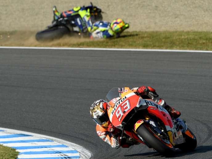 Marc Marquez (Honda) passe devant la Yamaha de l'ItalienValentino Rossi, couchée dans les graviers, le 16 octobre sur le circuit de Motegi (Japon).