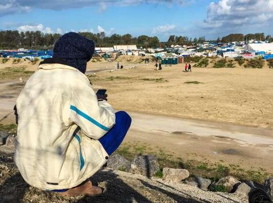 Un migrant regarde son téléphone dans la« jungle» de Calais le 17 octobre.