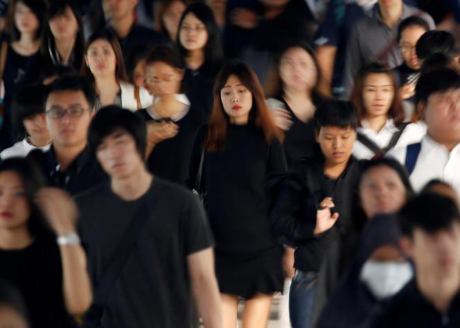 Des Thaïlandais vêtus de noir et de blanc, couleurs du deuil, dans une station de métrode Bangkok, le 17octobre.