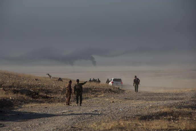 Des peshmergas s'approchent de Mossoul. Au loin, les djihadistes font brûler des pneus ou du pétrole, afinde gêner d'éventuelles interventions aériennes.