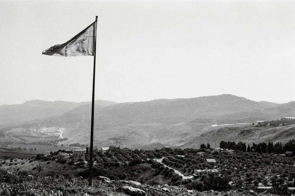 Établie par l'ONU en 2000 après vingt-deux ans d'occupation israélienne, la «ligne bleue» délimite une frontière provisoire entre le sud du Liban et Israël. Cette démarcation contestée, longue de 80kilomètres, la photographe française Catherine Cattaruzza, qui vit entre Beyrouth et Paris, a choisi de l'évoquer en pointillé. Ses images racontent une zone apparemment paisible, mais sur laquelle plane, à tout instant, la menace de la guerre. Ici, le drapeau du Hezbollahflottant à la frontière entre lesud du Liban et Israël. Au loin, Metula, en Haute-Galilée.