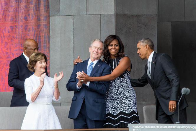 Michelle Obama prend l'ancien président républicain George W. Bush dans ses bras, lors de la cérémonie d'ouverture du musée de la culture et de l'histoire afro-américaine à Washington, le 24 septembre 2016.