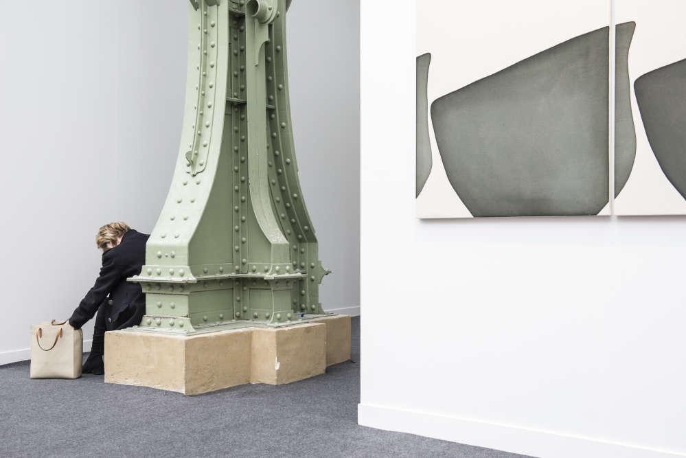Une visiteuse fait une pause appuyée sur un des piliers du Grand Palais.